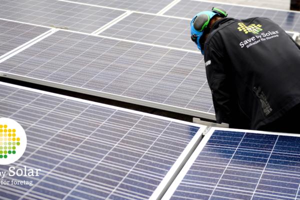 En installatör från Save by Solar installerar solceller i en solcellsanläggning